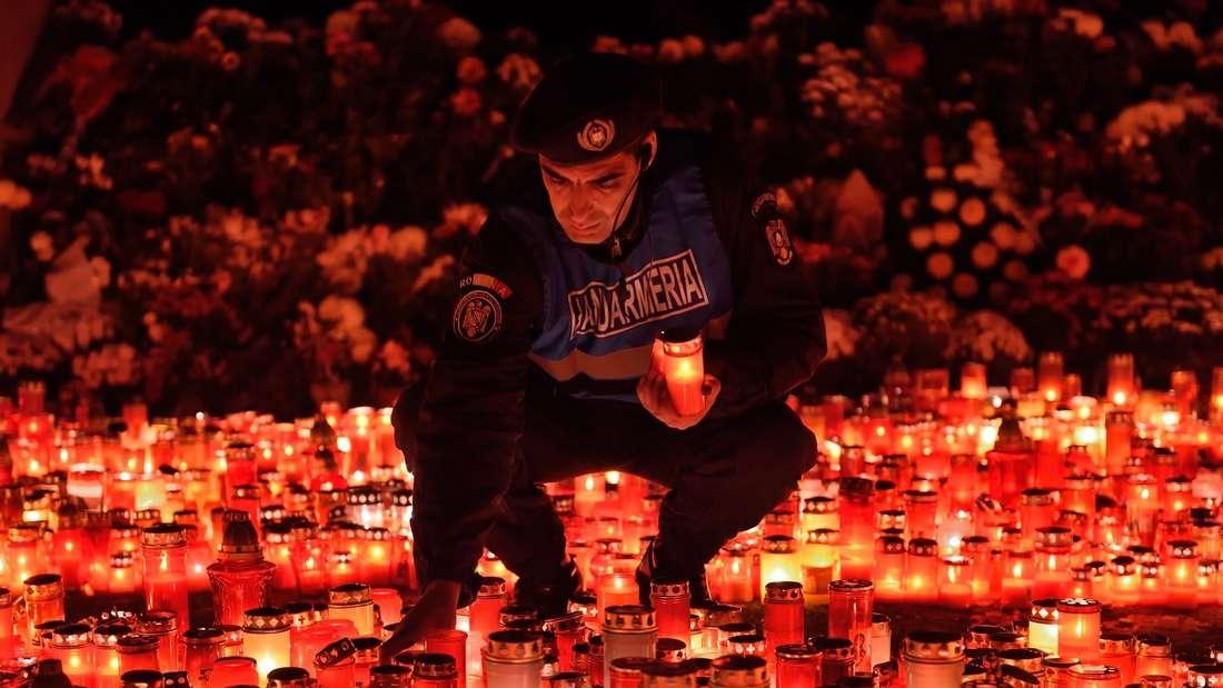 """Ein rumänischer Gendarm inmitten hunderter Kerzen, die von Trauernden vor dem Club """"Colectiv"""" in Bukarest aufgestellt wurden. In dem Club kamen nach bisherigen Erkenntnissen 31 Menschen bei einem Feuer ums Leben und weitere 200 wurden schwer verletzt."""