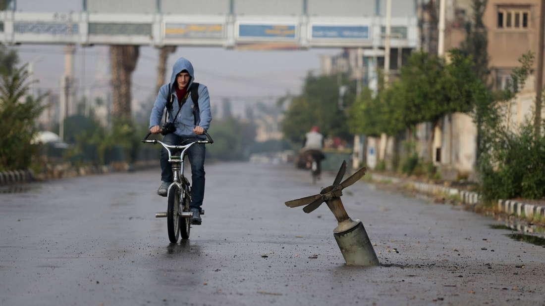 Ein Man fährt auf dem Fahrrad an einer explodierten Bombe im syrischen Damaskus vorbei.