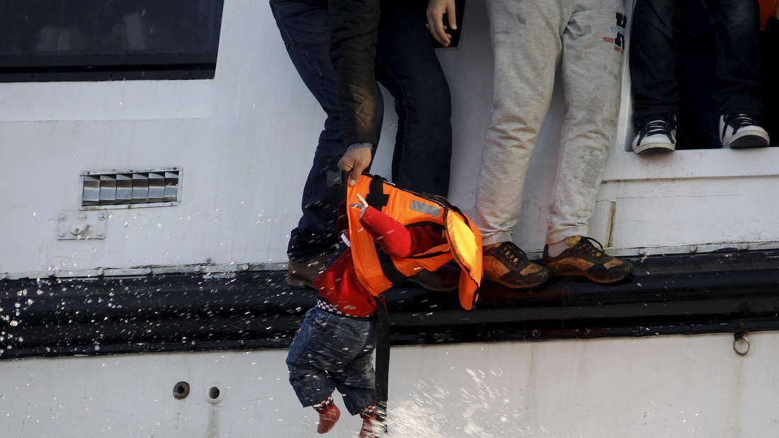 Ein geflüchteter Syrer versucht einen Jungen von einem sinkenden Katamaran an einen Rettungsschwimmer vor der Küste Griechenlands zu übergeben.