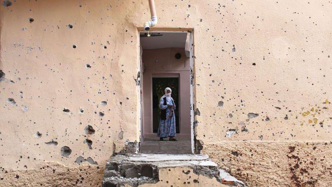 Eine Frau läuft durch ein von Schüssen gekennzeichnetes Haus in der von Kurden bewohnten türkischen Stadt Diyarbakır.