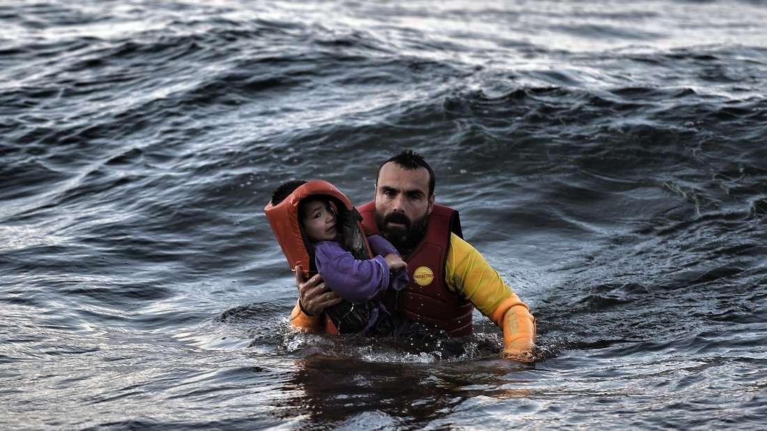 Ein spanischer Rettungsschwimmer bringt einen geflüchteten Jungen in Sicherheit. Das Boot des Jungen sank kurz zuvor vor der Küste der griechischen Insel Lesbos. Mindestens 17 andere Kinder starben während des Unglücks.