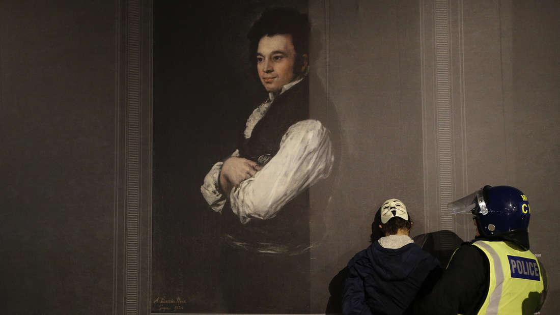 Ein Polizist hält einen Anhänger von Anonymous während einer Demonstration zur Guy Fawkes Night vor der National Gallery in London fest.