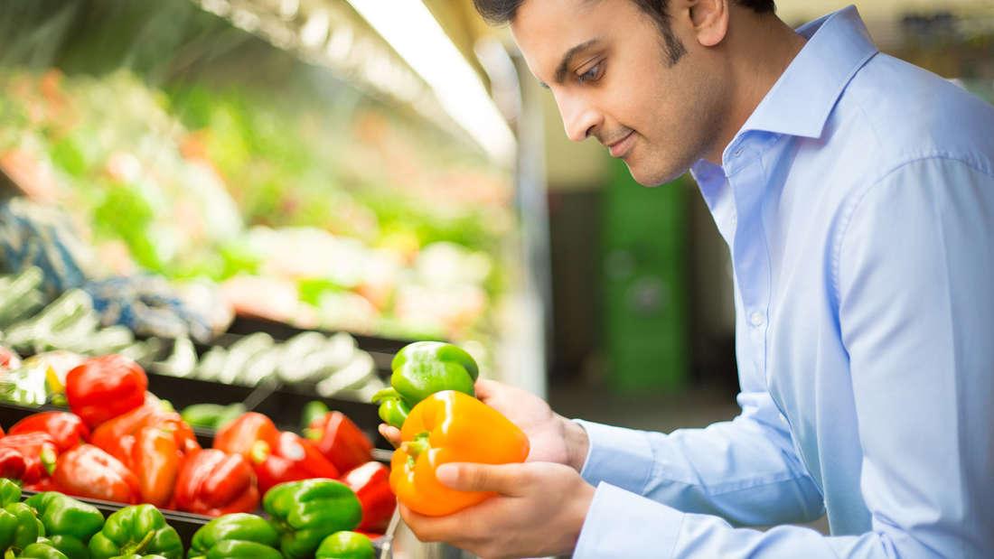 Ein Mann, der eine grüne und eine orange Paprika in den Händen hält.
