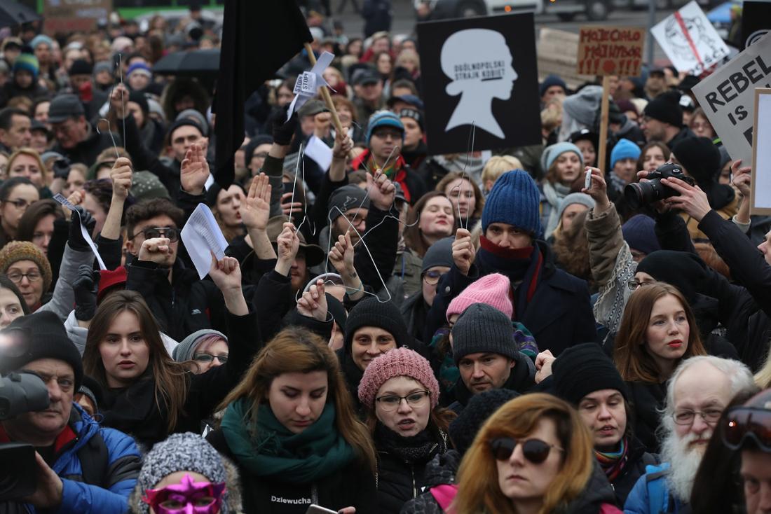 """Mit Kleiderbügeln demonstrieren Menschen für das Recht auf Abtreibung, wie hier im März 2018 in Warschau. Es soll daran erinnern, dass Frauen früher Drahtbügel nutzten, um selber Abtreibungen herbeizuführen. Seit 2016 protestieren zum der """"Czarny Protest"""" (deutsch: Schwarzer Protest) jedes Jahr Zehntausende."""