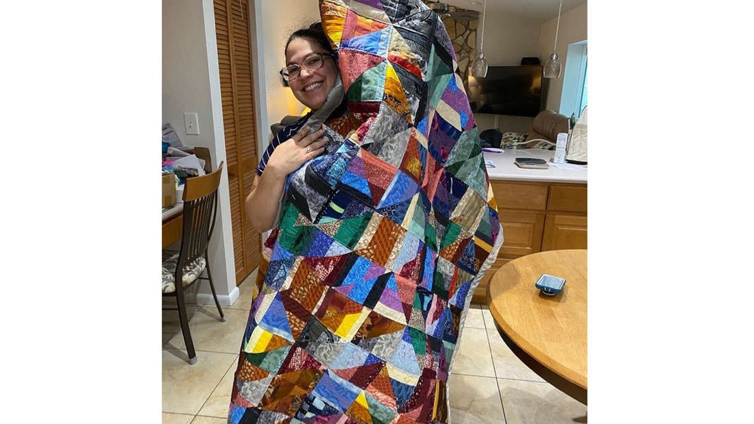Eine Frau, die stolz einen Quilt hochhält, der größer ist als sie