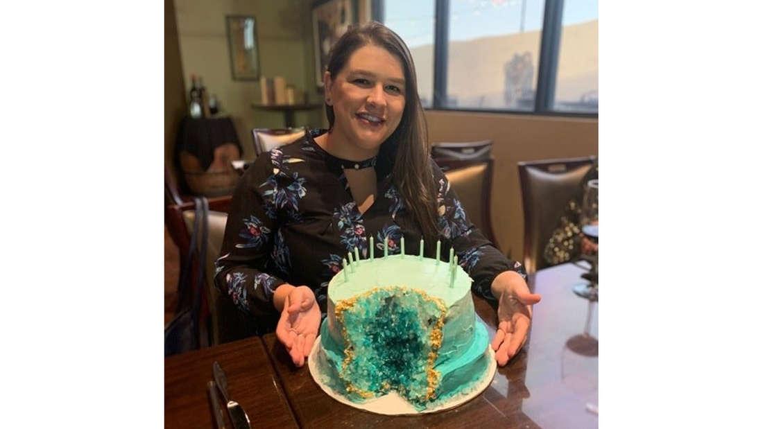 Ein Mädchen, die einen Kuchen hält, der wie eine Geode aussieht