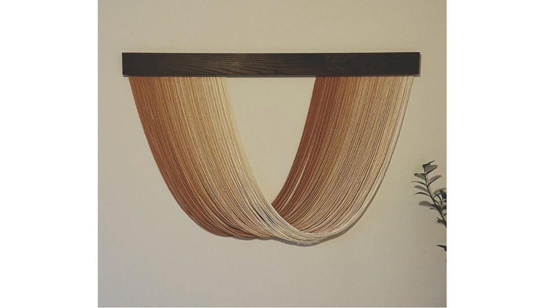 Makrameekunst aus braunen und hellbraunen Streifen, die einen Halbkreis bilden
