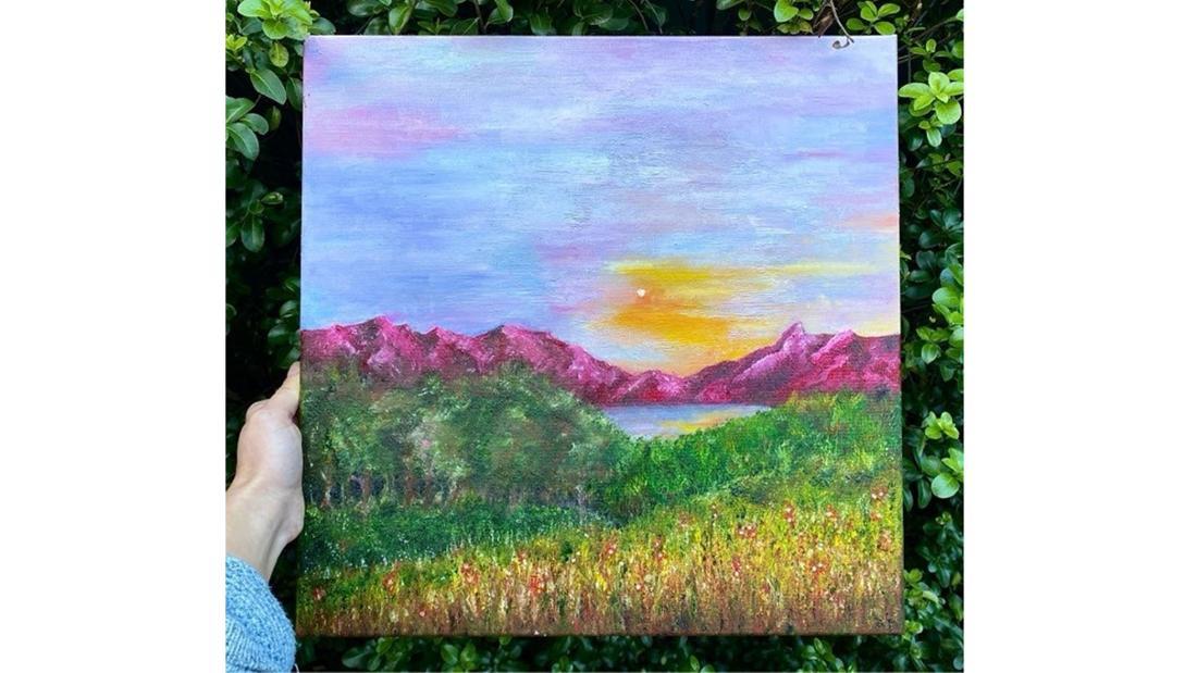 Ein Gemälde einer Berglandschaft mit pinken Bergen und blaurosa Himmel