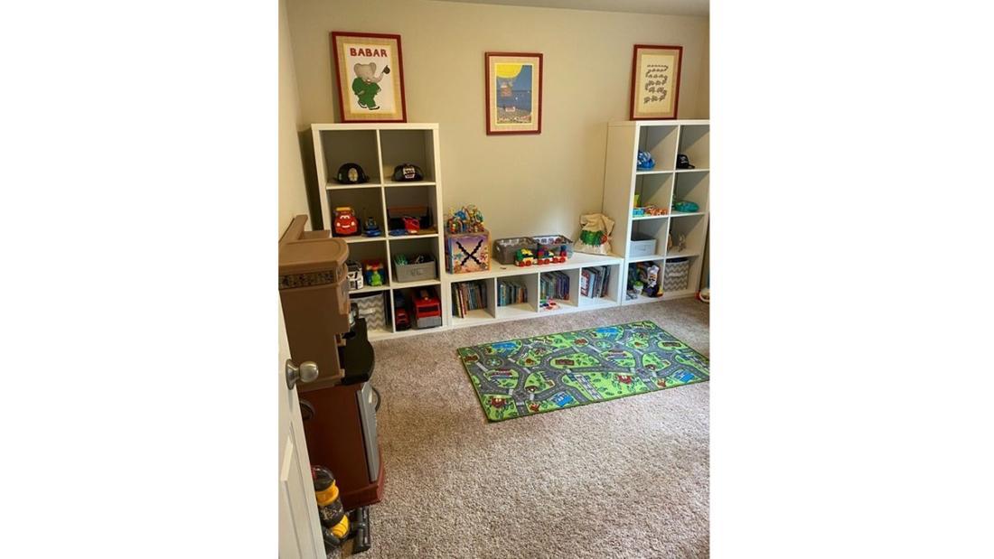 Ein Spielzimmer für Kinder mit Regalen, Spielsachen und einem Spielteppich
