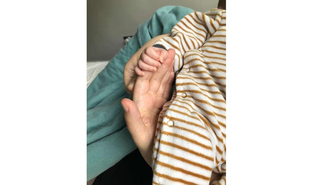 Ein Baby, das die Hand seiner*ihrer Mutter hält