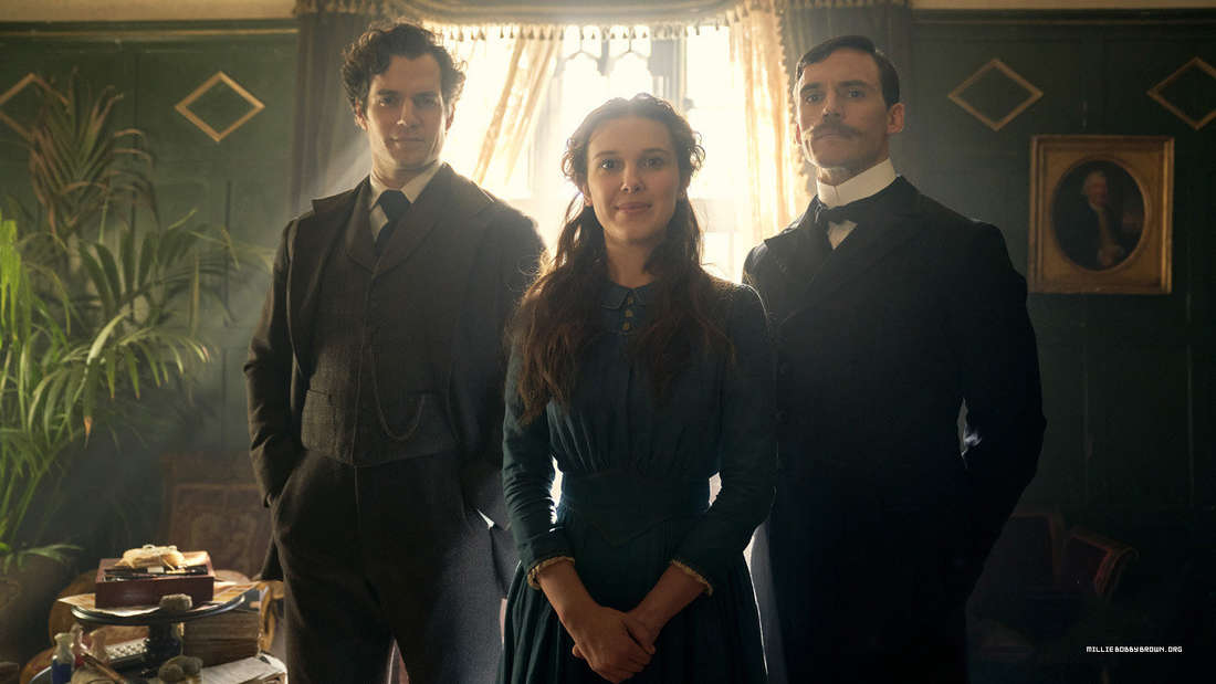 Enola Brown standing between her brothers, Sherlock (left) and Mycroft (right).