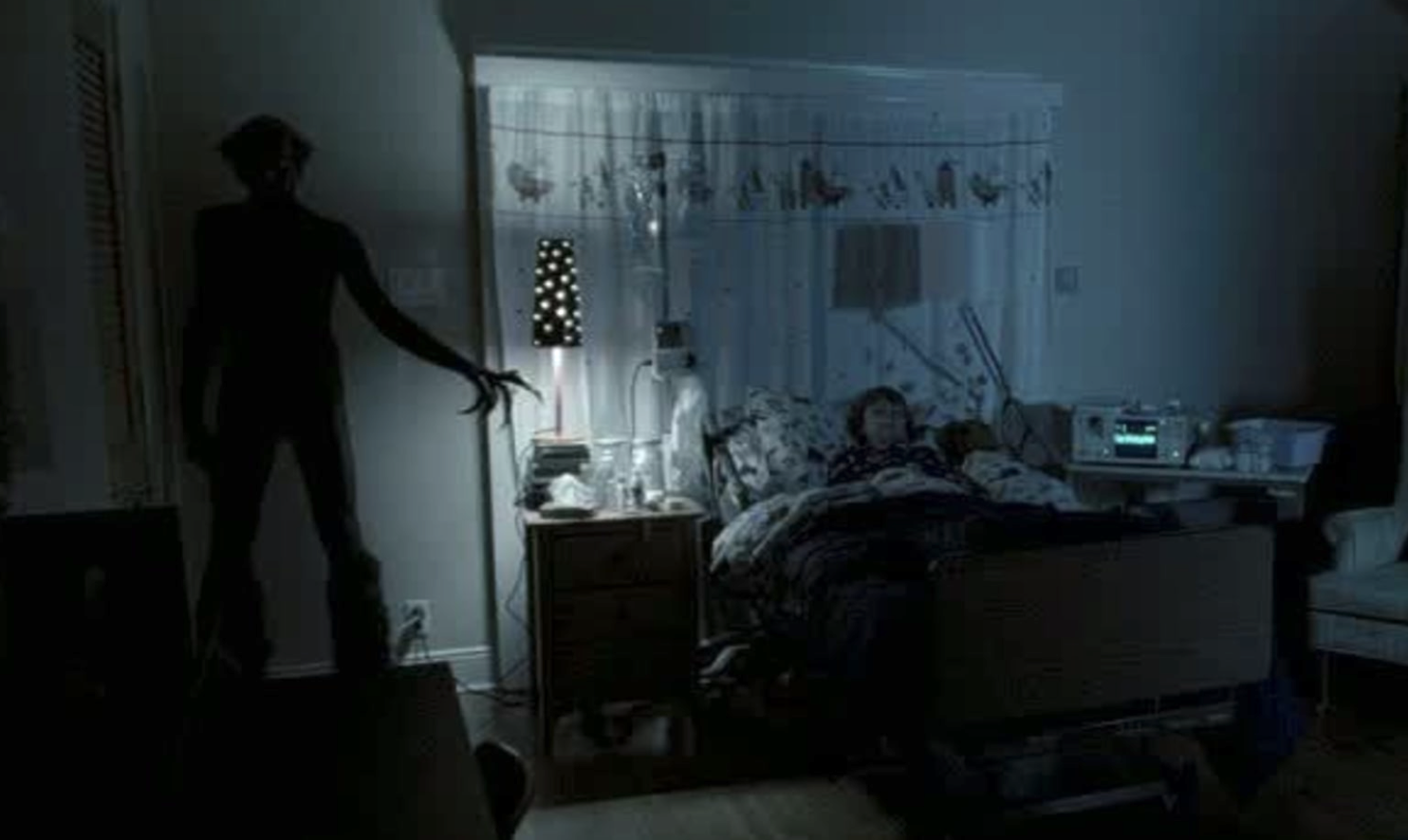 A young boy sleeps in a dark room while a creature stands in the corner