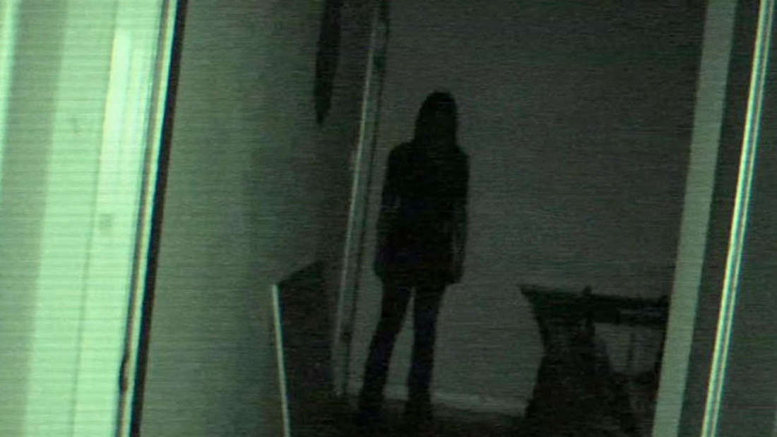 The dark shadow of a woman is at the end of the hallway