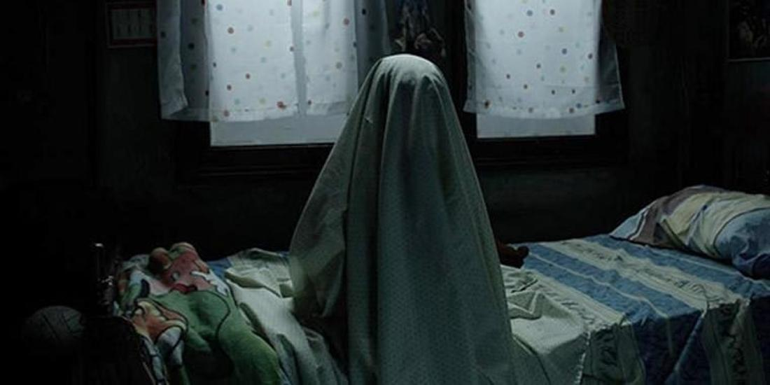 Someone with a sheet over their body sits on a bed