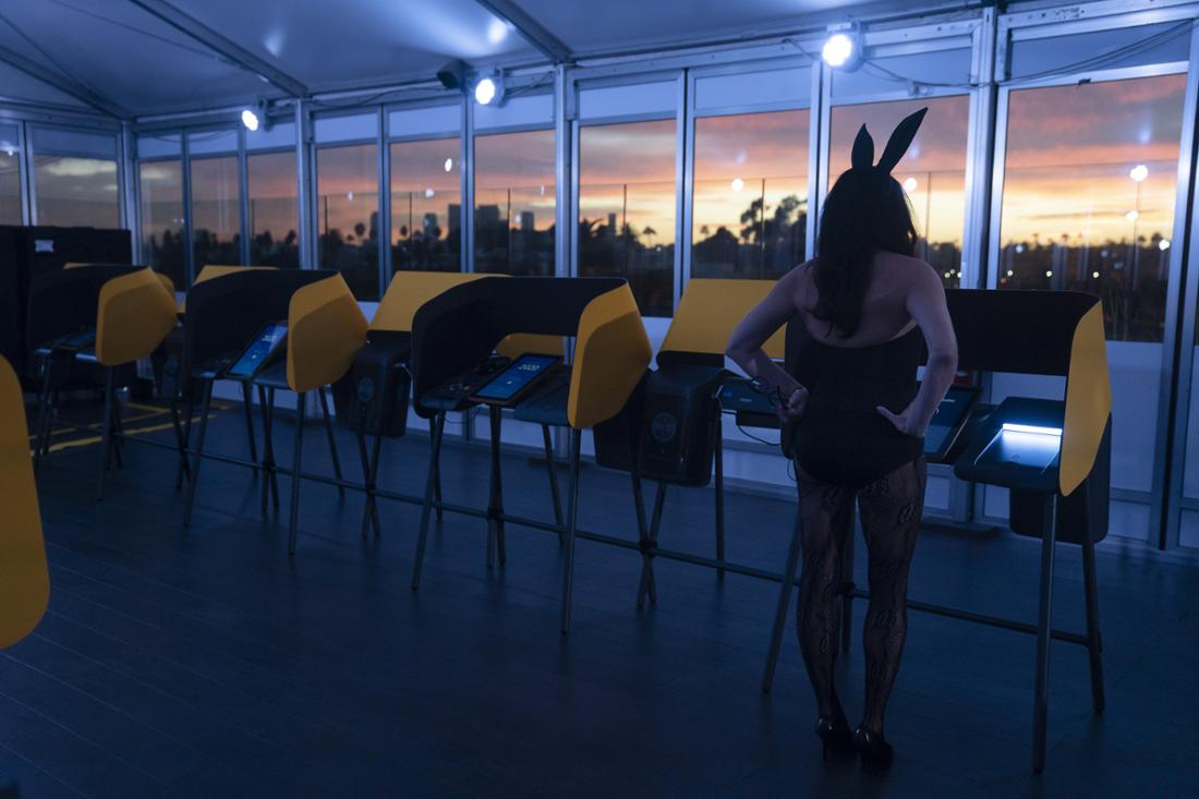 Woman in a Playboy Bunny costume at a voting booth on an enclosed rooftop.