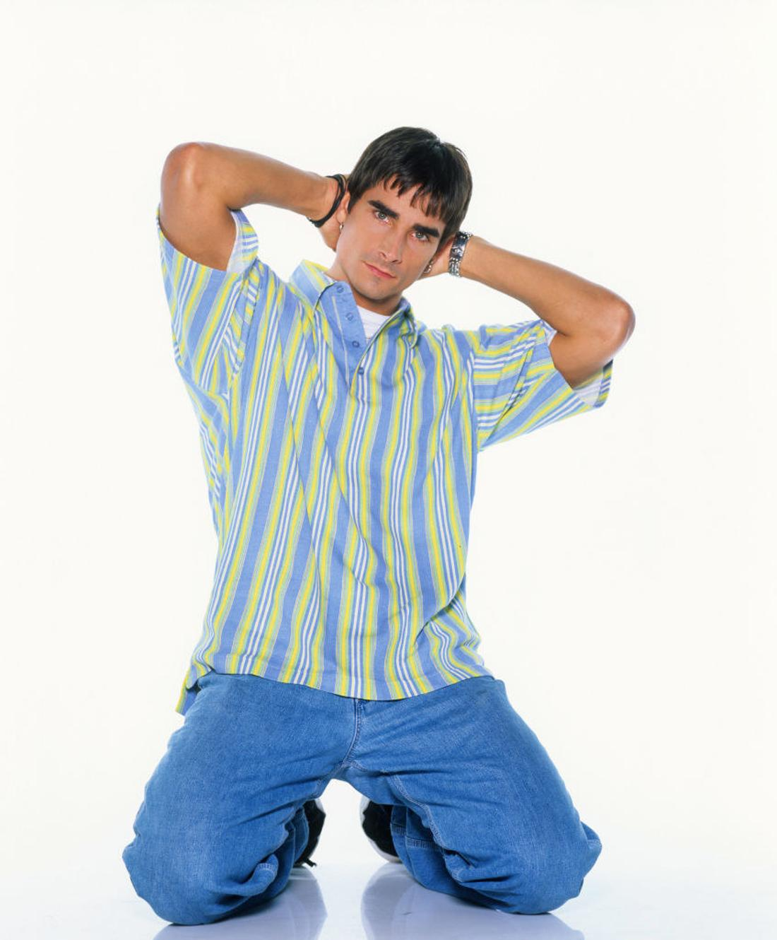Kevin Richardson on his knees with his hands on his head posing seductively