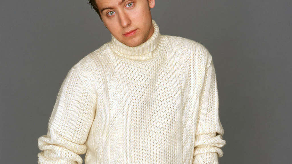Lance bass with a ripped turtleneck