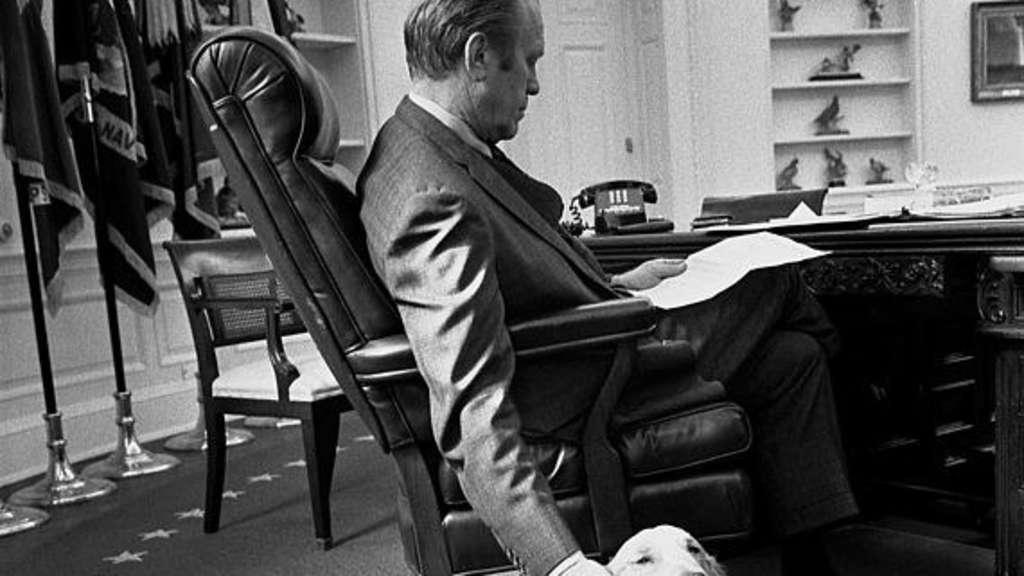 Ein Schwarz-Weiß-Foto von Präsident Gerald Ford, wie er seinen Golden Retriever im Oval Office streichelt.