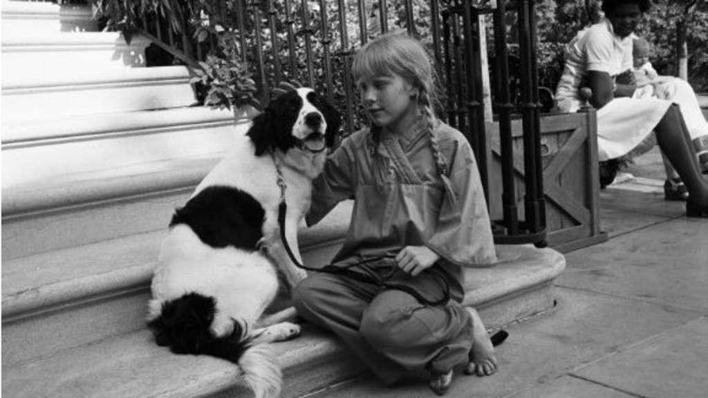Ein Schwarz-Weiß-Foto von Amy Carter, die mit ihrem Hund Grits auf einer Treppe sitzt.