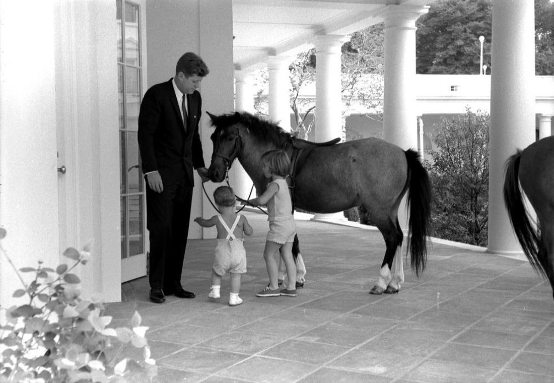 Präsident John F. Kennedy und seine Kinder, John F. Kennedy Junior und Caroline Kennedy stehen neben Carolines Pony Macaroni, auf einer Terrasse vor dem Oval Office.