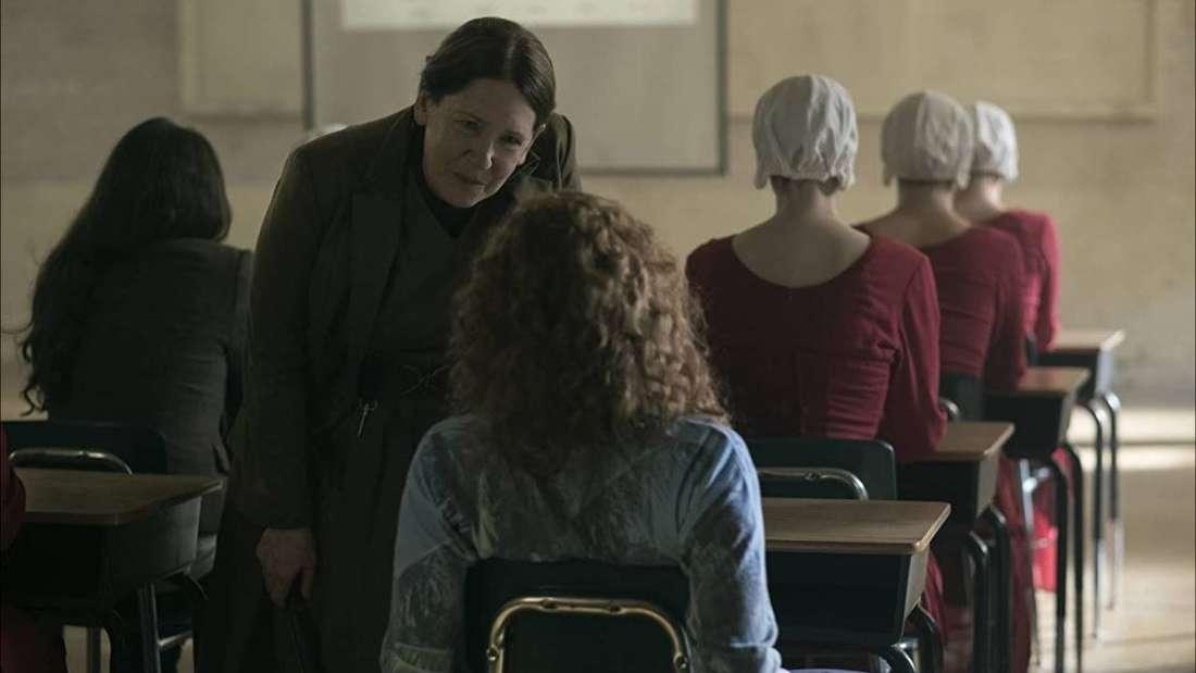 Mehrere Frauen sitzen in einem Klassenzimmer. Manche tragen Alltagskleidung, andere rote Kleider und weiße Hauben. Eine streng gekleidete Frau beugt sich zu einem Mädchen herunter, das unordentlich auf ihrem Platz sitzt.