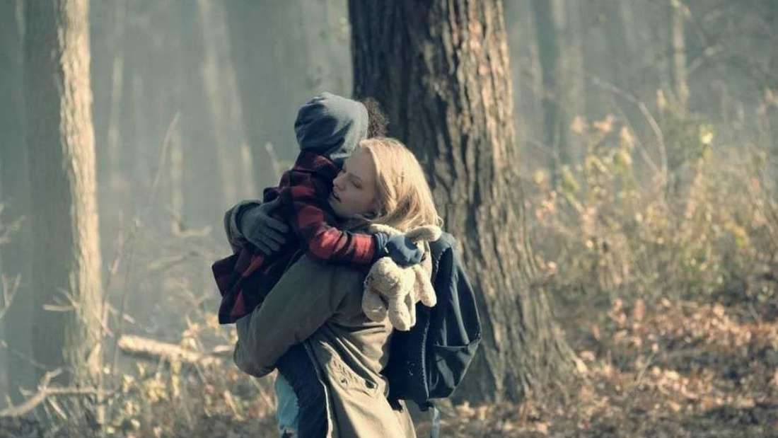 June läuft mit ihrer Tochter auf dem Arm durch einen Wald.