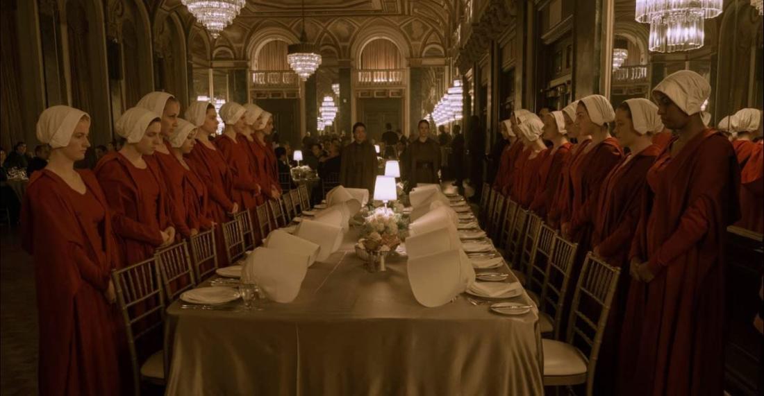 Die Mägde stehen hinten ihren Stühlen, vor einer elegant gedeckten Tafel.