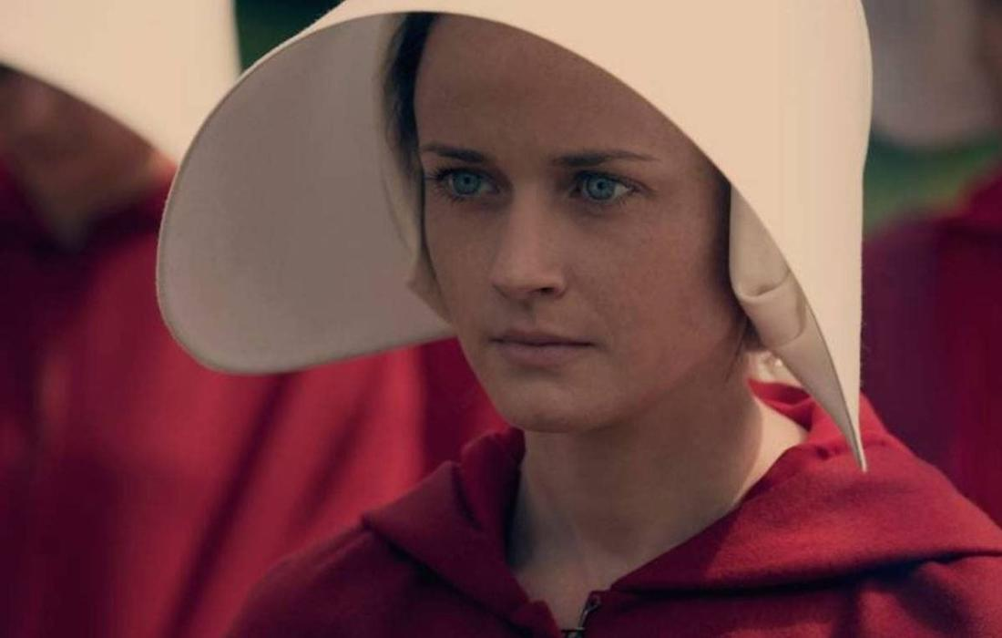 Eine Nahaufnahme von Emily in einem roten Mantel und einer weißen Haube.