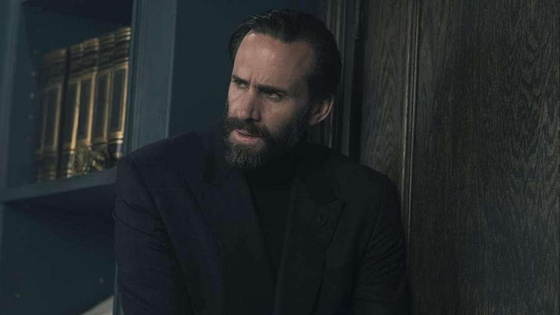 Fred Waterford steht neben einem Bücherregal: ein Mann in schwarzen Anzug, mit dunklen Haaren und Bart.