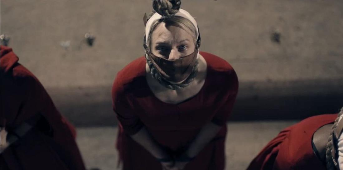 June steht neben zwei anderen Mägden mit einem Seil um den Hals und verbunden Mund. Sie blickt mit Tränen in den Augen nach oben.