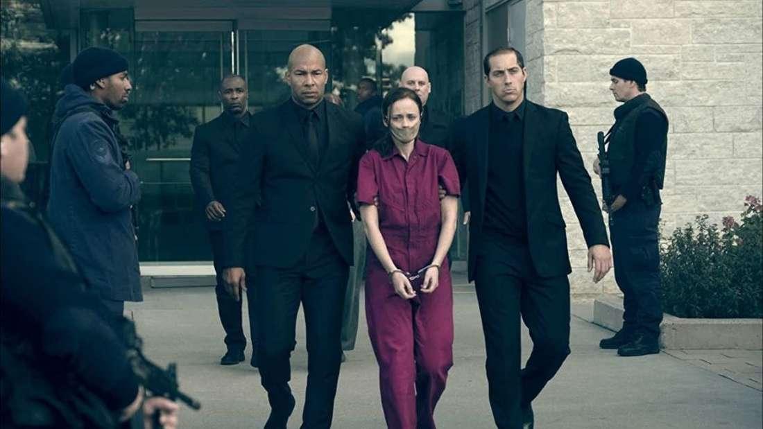 Emily trägt eine rote Sträflingsuniform, ist in Handschellen gelegt und trägt eine Maske über dem Mund. Zwei Männer in schwarzen Anzügen führen sie aus einem Gebäude, um sie herum stehen noch mehr Männer in schwarz, bewaffnet mit Maschinengewehren.