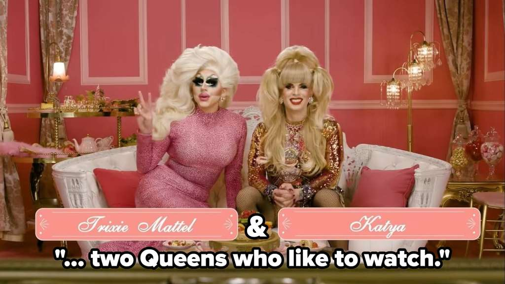 Drag Queens Trixie und Katya sitzen auf einer Couch, in einem pink eingerichteten Wohnzimmer. In der Bauchbinde steht: Trixie Mattel and Katya, two Queens who like to watch.