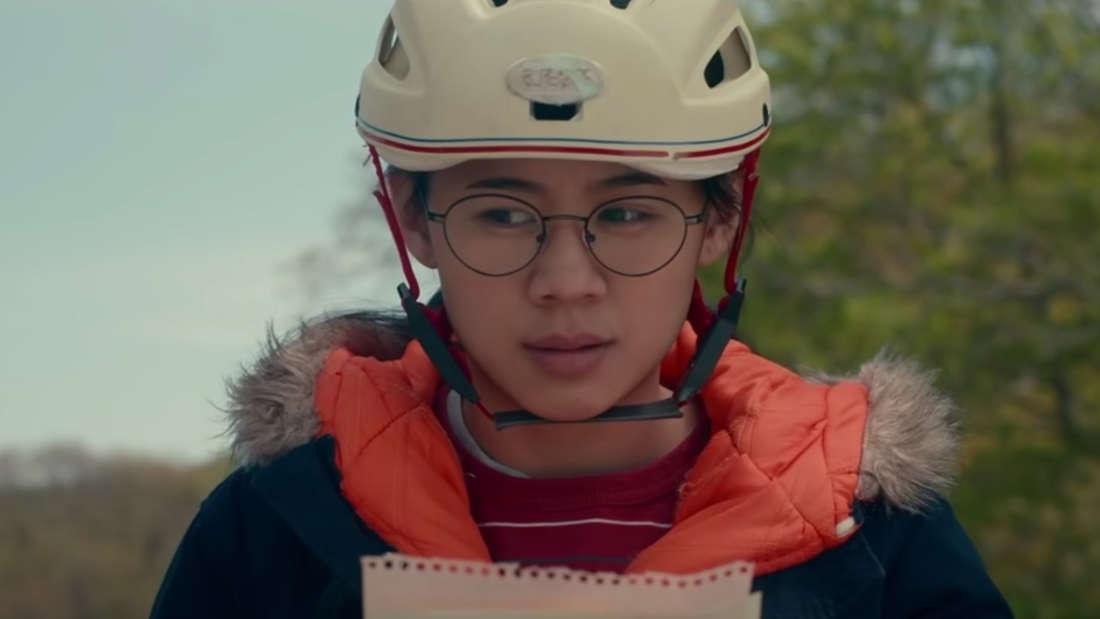 """Der Screenshot zeigt Ellie aus dem Netflix Film """"Nur die halbe Geschichte"""". Sie hält einen Brief in der Hand."""