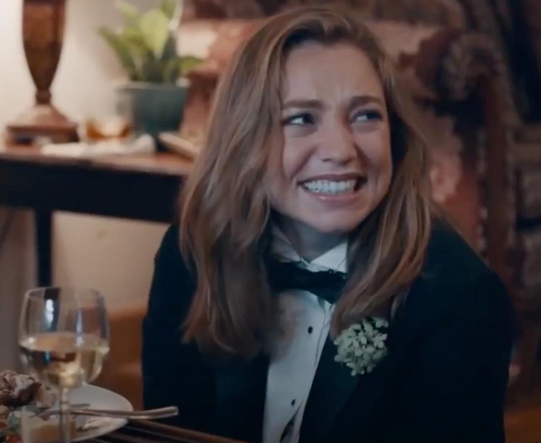 """Der Screenshot zeigt Cyd aus dem Film """"Princess Cyd"""", die in einem Tuxedo vor einem Tisch sitzt und beschämt grinst."""