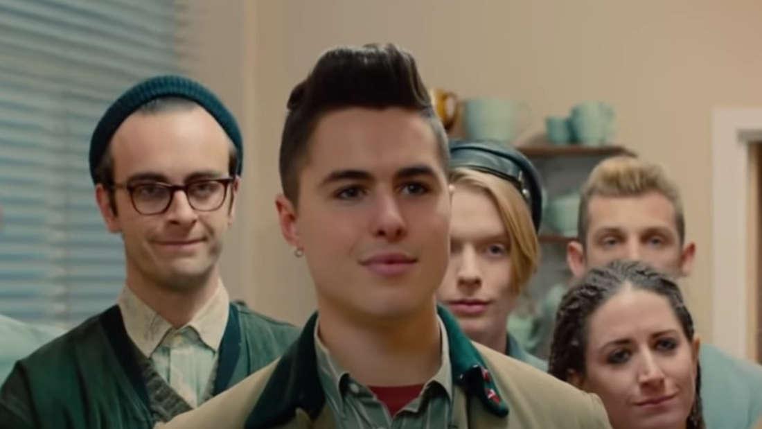 """Der Screenshot zeigt die Hauptcharaktere aus dem Film """"Pride"""", die zusammen stehen und verdutzt gucken."""