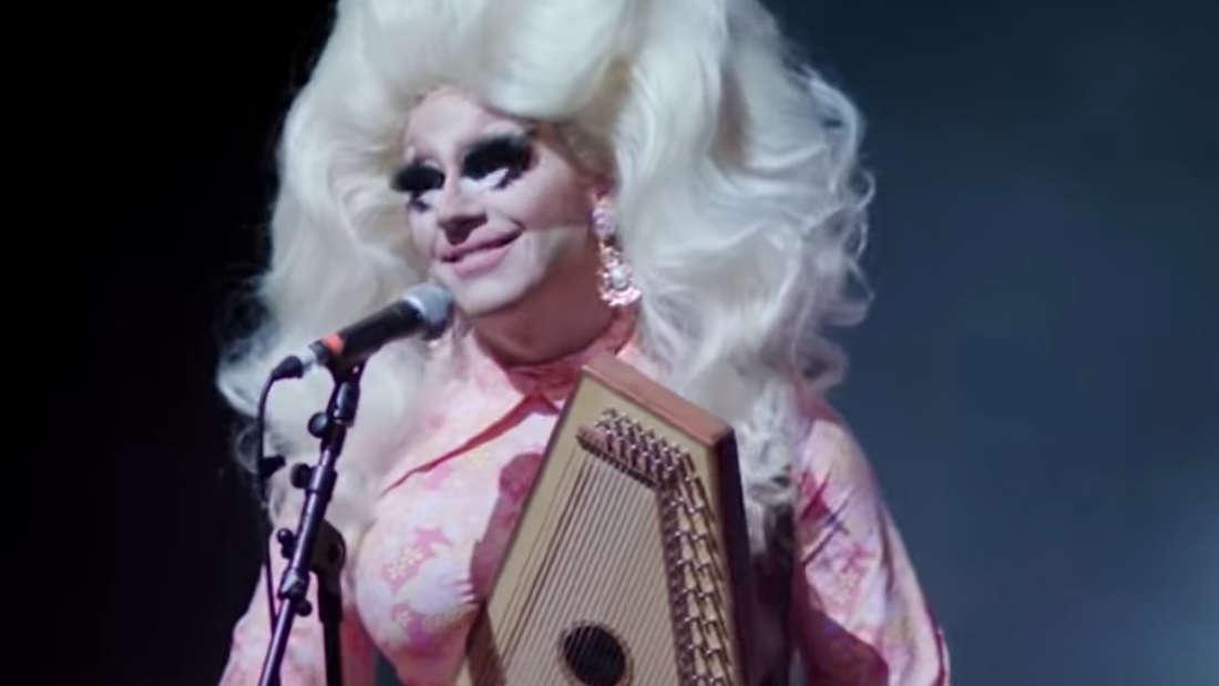 """Der Screenshot zeigt die Dragqueen Trixie Mattel aus ihrem Film """"Moving Parts"""". Sie hält ein Instrument in der Hand und lächelt."""