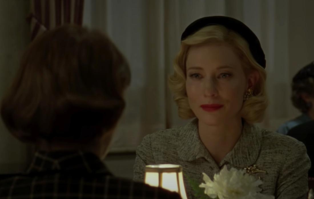 """Der Screenshot zeigt Carol aus dem Film """"Carol"""", die ihrer Freundin in einem Restaurant gegenübersitzt. Sie sieht amüsiert aus."""