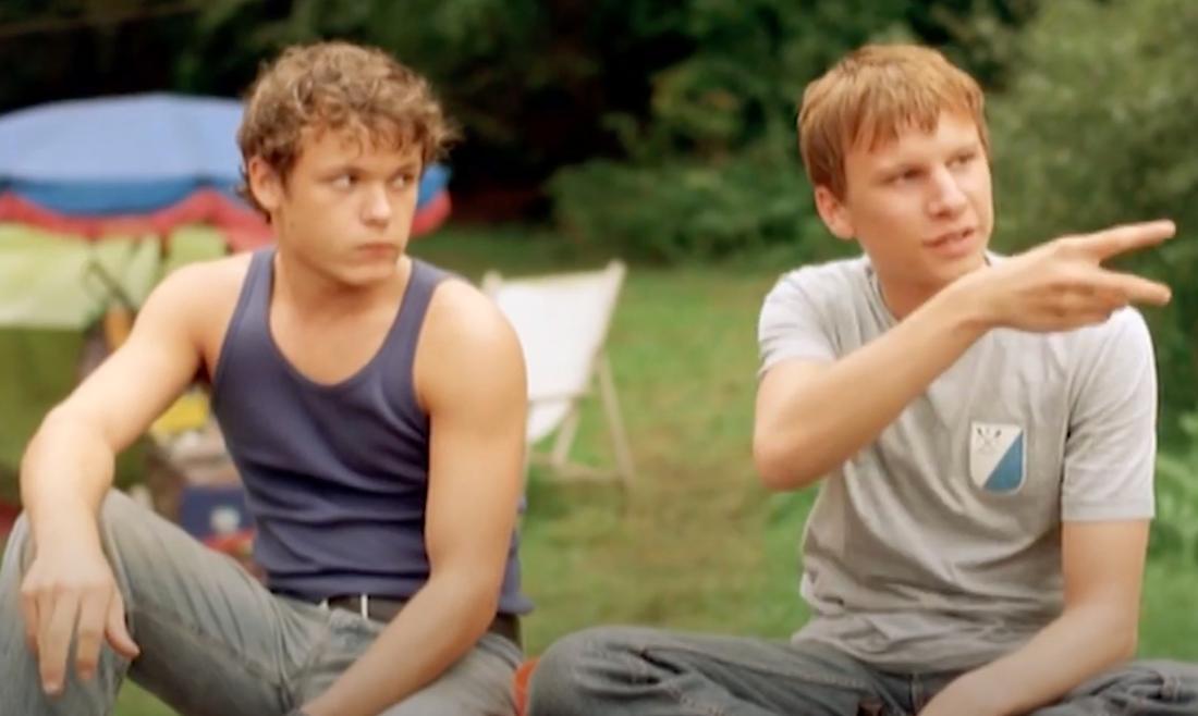 """Der Screenshot zeigt Leo und Tobi aus dem Film """"Sommersturm"""", die nebeneinander sitzen und skeptisch aussehen."""
