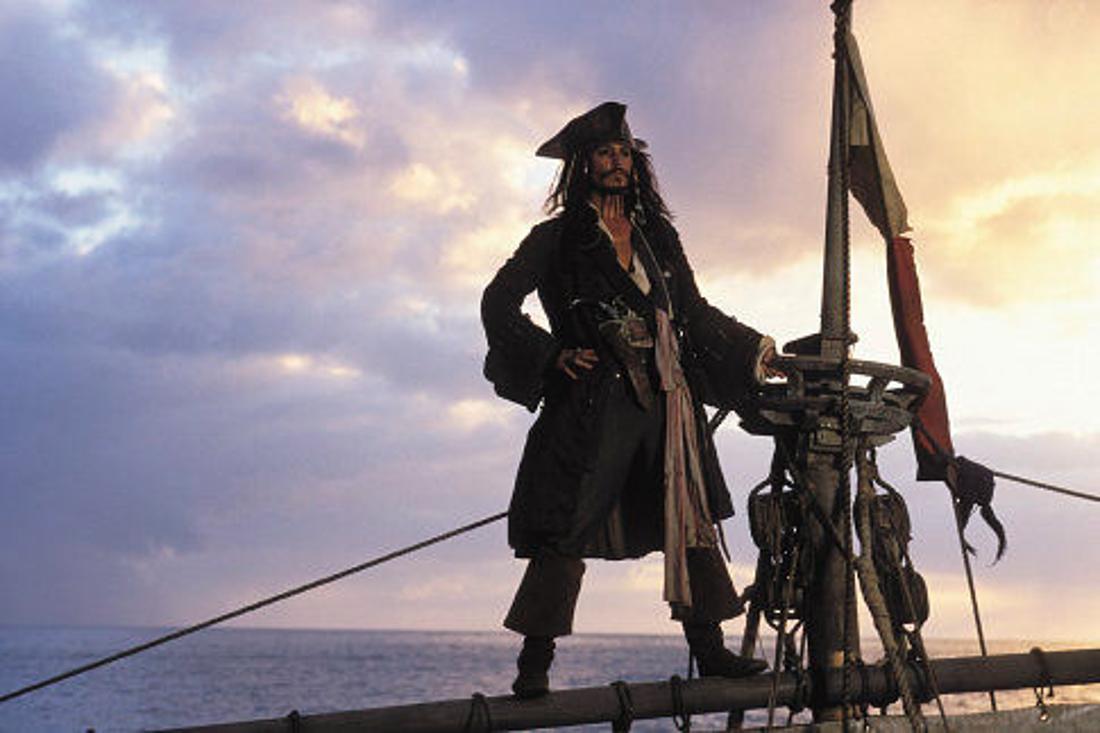 Johnny Depp als Captain Jack Sparrow steht an der Spitze eines Schiffsmasts.
