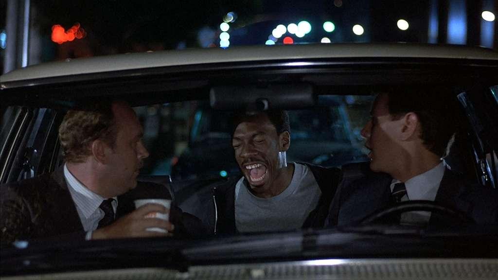 Eddie Murphy als Beverly Hills Cop Axel Foley überrascht seine Kollegen in einem Auto.