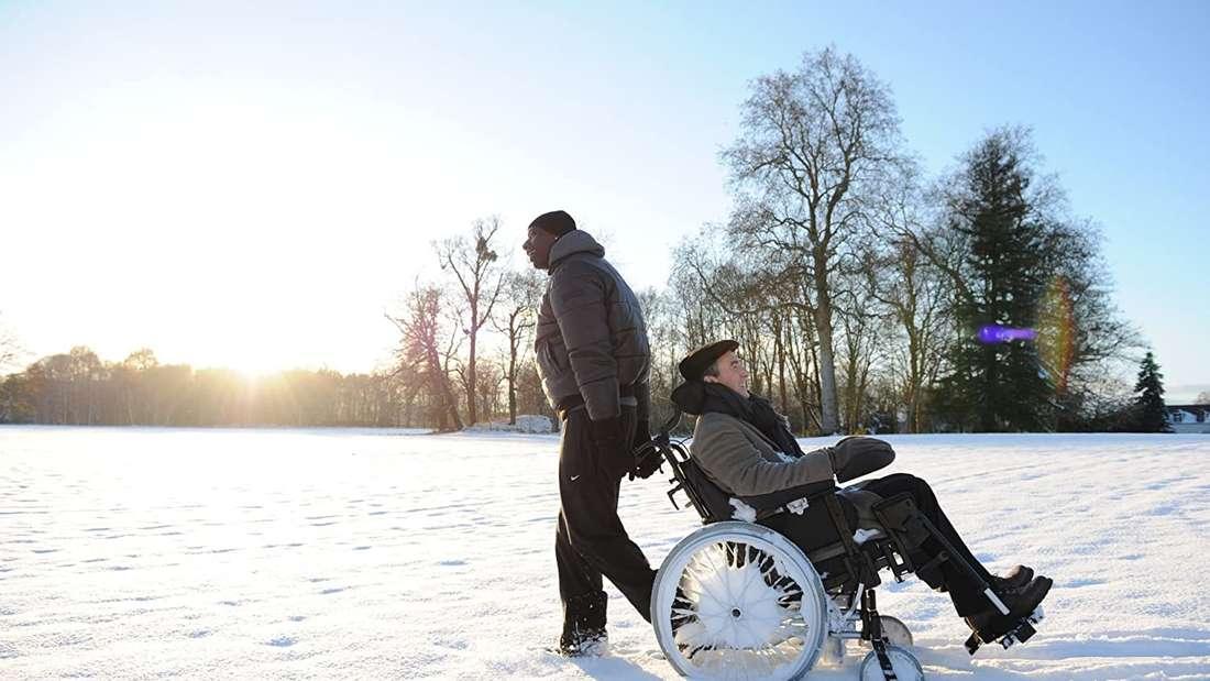 Der im Rollstuhl sitzende Philippe wird von seinem Pfleger Driss durch den Schnee gezogen.