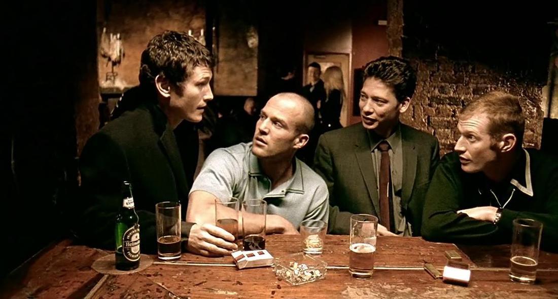 """In dieser Szene des Films """"Bube, Dame, König, grAS"""" unterhalten sich die vier Protagonisten in einer Bar."""