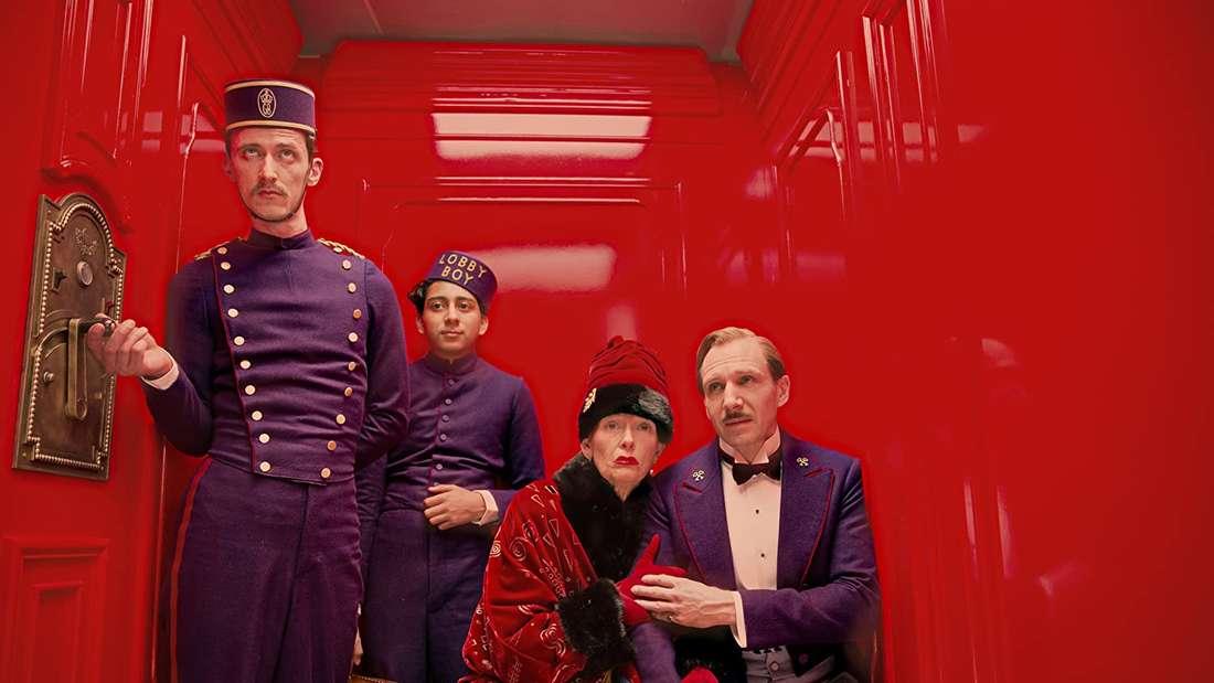 Ralph Fiennes als Concierge des Grand Budapest Hotels fährt mit Angestellten und einer älteren Dame im Aufzug des Hotels.