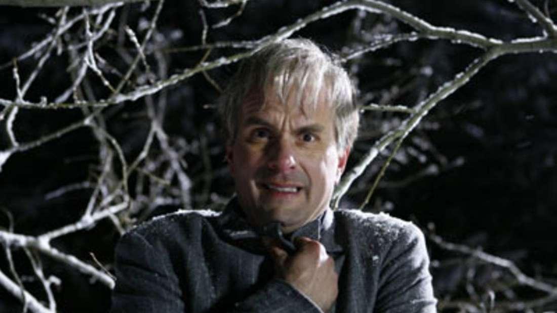 Der Screenshot zeigt Tilmann, der frierend auf einem Baum sitzt und sich das Jacket zuhält.