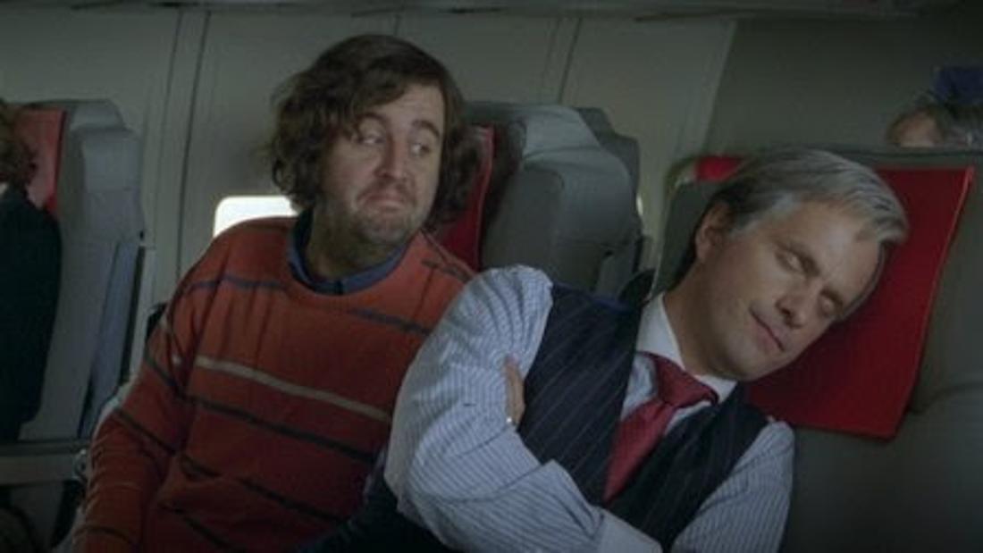 Hilmar und Tilmann aus dem Film sitzen zusammen im Flugzeug. Während Tilmann schläft, versucht Hilmar ein Gespräch zu beginnen.