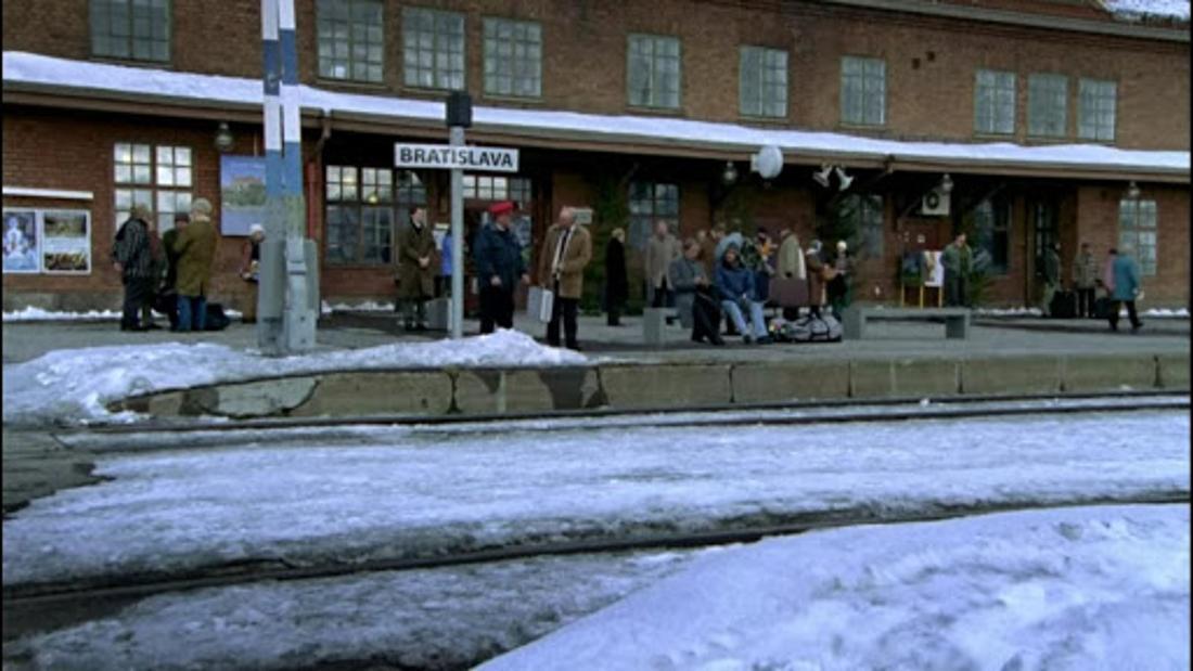 Hilmar und Tilmann aus dem Film sitzen gemeinsam am Bahnsteig in Bratislava. Es sind viele Leute und viel Schnee zu sehen.
