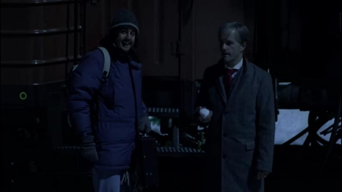 Hilmar und Tilmann aus den Film stehen gemeinsam vor einem Zug. Es ist dunkel und Hilmar sieht belustigt aus, während Tilmann einen Schneeball in der Hand hält.
