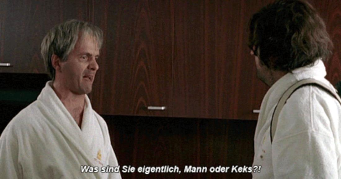 """Tilmann und Hilmar stehen sich im Film in Bademänteln im Hotel gegenüber. Tilmann sieht genervt aus, als er Hilmar fragt """"Was sind Sie eigentlich, Mann oder Keks?"""""""