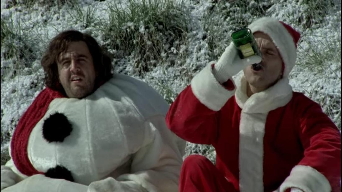 Im Film sitzen Hilmar und Tilmann im Schnee- und Weihnachtsmannkostüm im Schnee. Tilmann trinkt Alkohol aus der Flasche.
