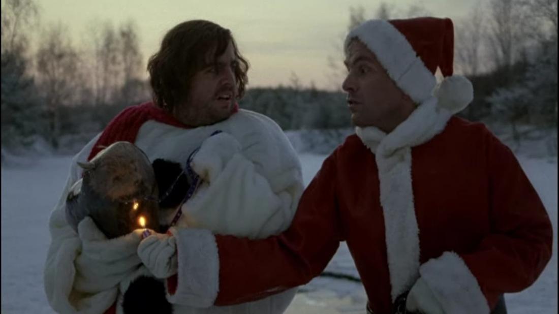 Hilmar und Tilmann stehen gemeinsam im Schnee. Sie halten einen Hund in der Hand, der eingefroren ist und den sie mit einem Feuerzeug auftauen.
